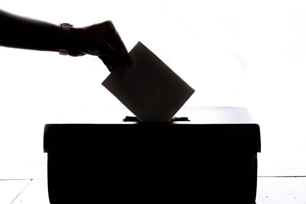 Image of a hand submitting a ballot into a ballot box.
